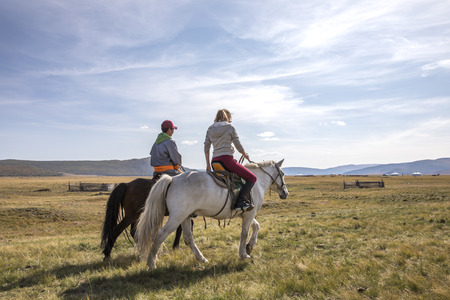 couple riding horses in a landscape of northern Mongolia