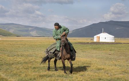 Huvsgul, Mongolia, September 6th, 2017: mongolian man riding a horse in northern mongolian landscape