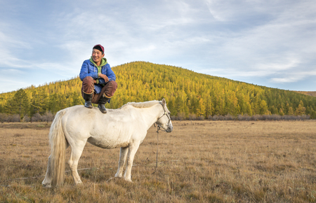 mongolian man sitting on a horse and smoking a cigarette