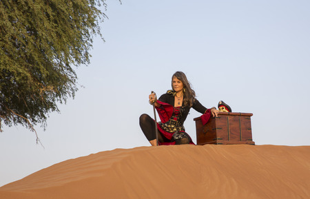 loot: lady pirate in a desert with a treasure Stock Photo
