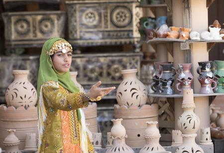 Nizwa, Oman, November 10th, 2017: omani girl dressed in traditional clothing singing Editorial