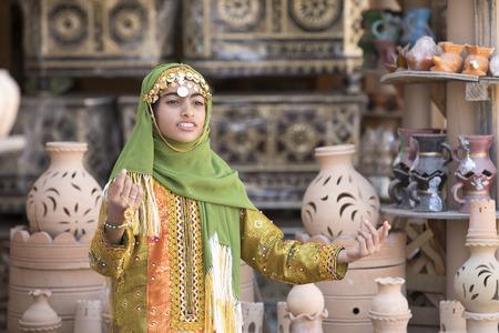Nizwa, Oman, November 10th, 2017: omani girl dressed in traditional cloting singing Editorial