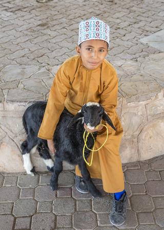 Nizwa, Oman, November 10th, 2017: omani boy with a goat at a market
