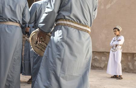 Nizwa, Oman, December 1st, 2017: omani boy looking at men celbrationg a national day by dancing national dances