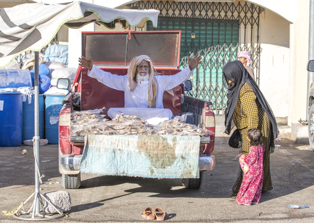 Sinaw, Oman, November 30th, 2017: bedhouin man selling dry fish at a market