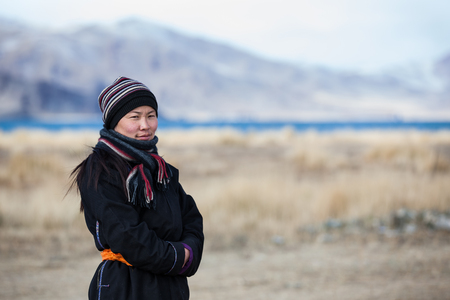 ULGII, MONGOLIA - CIRCA OCTOBER 2015: older Mongolian lady outside in a landscape of Western Mongolia