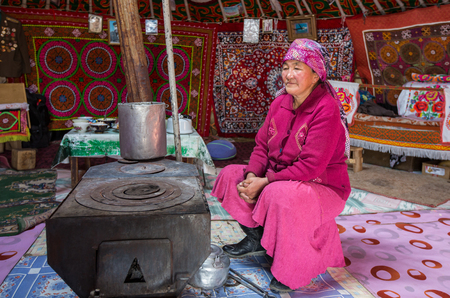 ULGII, MONGOLIA - CIRCA OCTOBER 2015: older Mongolian lady is sitting next to a stove in her yurt in western Mongolia, near Bayan Ulgii Stok Fotoğraf - 93729322