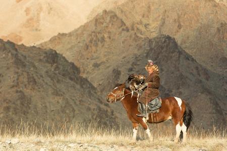 Baya Olgii, Mongolia, September 2015: Kazakh man training his alert Golden Eagle Redactioneel