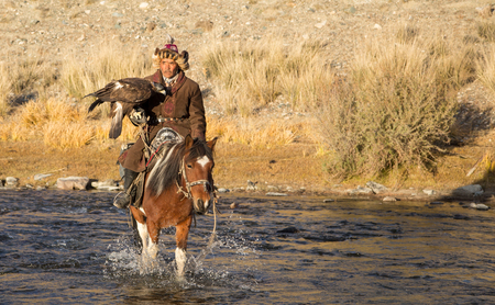 Bayan Ulgii, Mongolia, September 30th, 2015: Mongolian eagle hunter with his eagle and horse