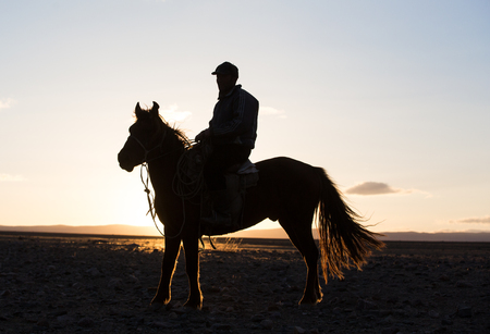 Bayan Ulgii, Mongolia, October 2nd, 2015: Man with his horse in Mongolian landscape at sunset