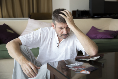 stressed middle aged man looking at his credit cards