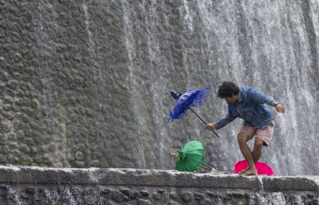 Bali, Indonesia, September 11th, 2016: Young Indonesian boys having fun at a waterfall Editorial