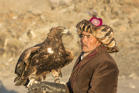 Bayan Ulgii, Mongolia, October 2nd, 2015: Man with his horse and Altai Golden eagle at sunset