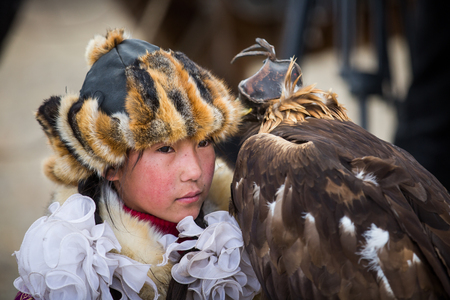 BAYAN ULGII, MONGOLIA - CIRCA OCTOBER 2015: young lady eagle hunter with her eage 新聞圖片