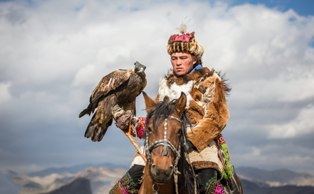 BAYAN ULGII, MONGOLIA - CIRCA OCTOBER 2015: Kazakh man in traditional clothing  on his horse