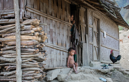 Chittagong, Bangladesh, 7th March, 2016:kid sitting outside his house at a countryside
