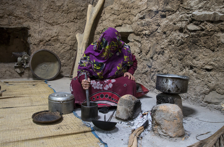 Al Hamra Oman, Febrary 2nd, 2018: omani woman making preparations in the kitchen of traditional house Editorial