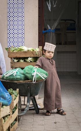 Nizwa, Oman, Febrary 2nd, 2018: omani kid at a vegetable market
