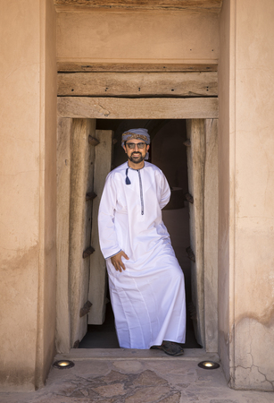 Arab man in traditional Omani outfit coming out of a door