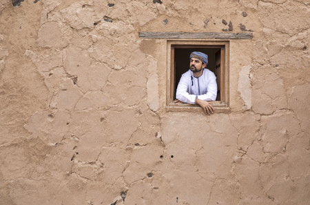 Arab man in traditional Omani outfit looking out of a window