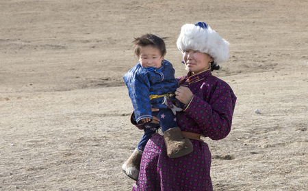 Hatgal, Mongolia, 2nd March 2018: mongolian woman with her baby in northern Mongolian steppe Banco de Imagens - 98938775