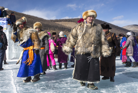 Hatgal, Mongolia, 4th March 2018: mongolian people dressed in traditional clothing walking on a frozen lake Khuvsgul during an ice festival