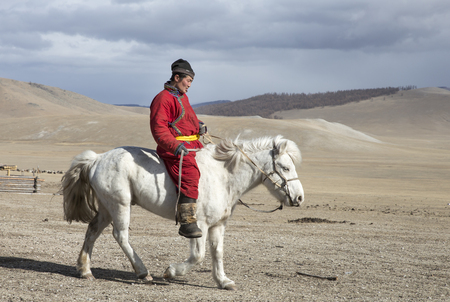 Hatgal, Mongolia, 3rd March 2018: mongolian man on a white horse in a steppe of northern Mongolia Editorial
