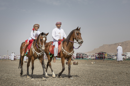 Ibri, Oman, 28th April 2018: omani father and son riding arabian horses