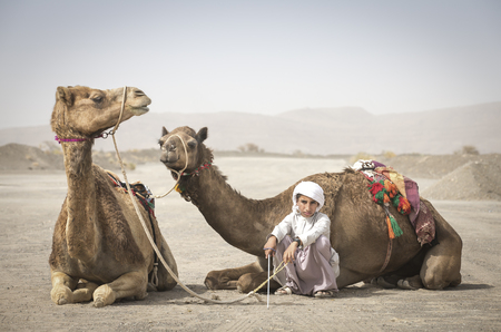 Ibri, Oman, 28th April 2018: bedouin kid with his camels on a countryside of Oman Editorial