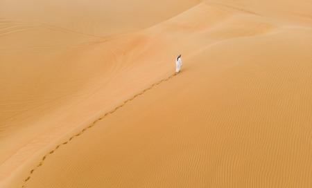 Hombre en traje tradicional emiratí caminando en las enormes dunas de arena del desierto de Liwa Foto de archivo