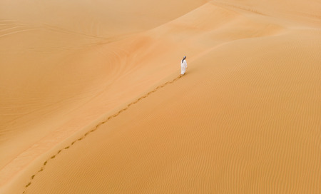 Mann im traditionellen emiratischen Outfit zu Fuß in massiven Sanddünen der Liwa-Wüste? Standard-Bild