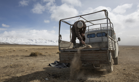 Bayan Ulgii, Mongolia, 29th September 2015: mongolian kazakh nomad man cleaning the back of the car in preparation of moving their yurt to a new location Editorial