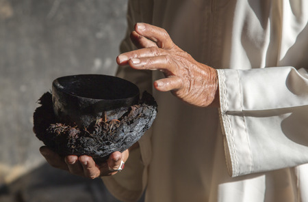 old man explaining how rose water gets made in traditional way