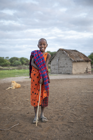 Same, Tanzania, 7th June, 2019:  young Maasai kid in his boma, with his house at the background Editorial