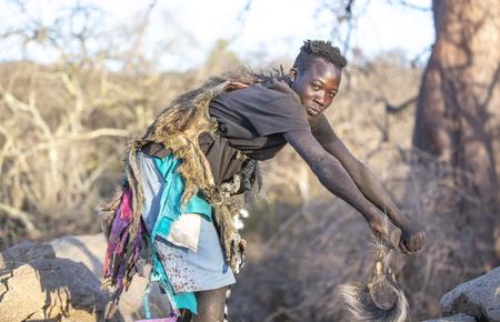 lake Eyasi, Tanzania, 11th September 2019: hadzabe man showing how baboons walk