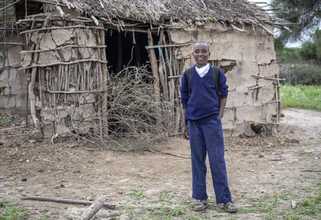 Same, Tanzania, 5th June, 2019:  Maasai boy in his school uniform in front of his home