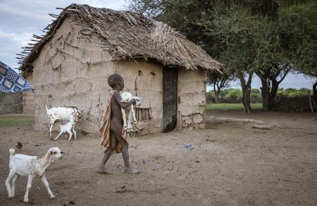 Same, Tanzania, 5th June, 2019:   Maasai  boy keeping baby goats from escaping their house