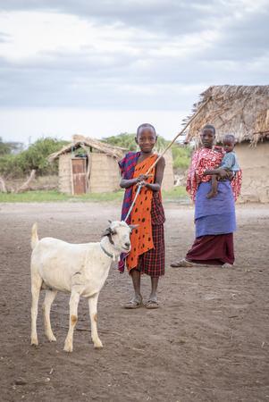Same, Tanzania, 7th June, 2019:  young Maasai man walking with his goat in a boma