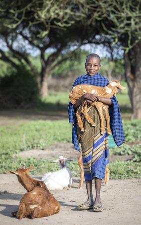 same, Tanzania, 4th June 2019: maasai boy with a baby goat Editorial