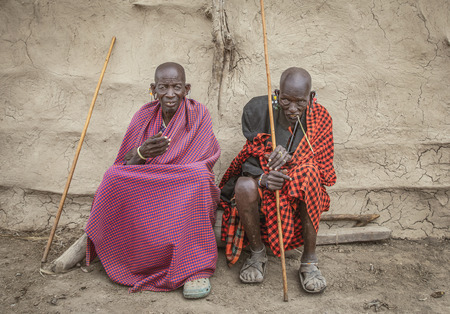 Same, Tanzania, 4th June, 2019: old masai man resting and cleaning his teeth with a tree branch