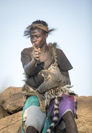 Lake Eyasi, Tanzania, 11th September 2019: Hadzabe young man in animal fir clothing, resting