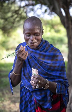 Same, Tanzania, 4th June, 2019:  Maasai man eating bone marrow out of a cows foot