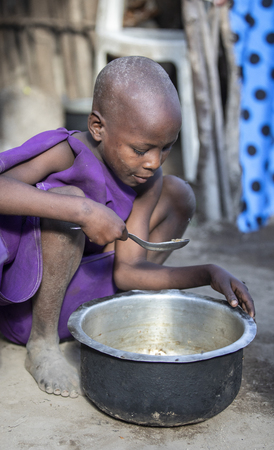 Same, Tanzania, 4th June 2019: young Maasai girl scraping food leftovers off a pot so she can eat more