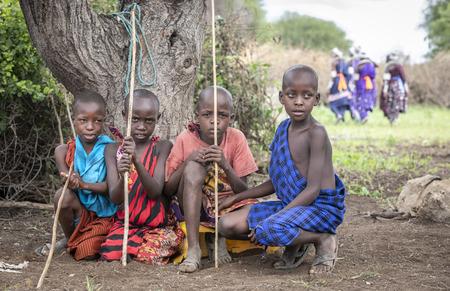 same, Tanzania, 5th June 2019: young maasai boys resting under a tree Editorial