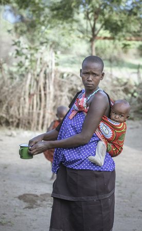 Same, Tanzania, 4th June, 2019:   Maasai  woman with her baby on her back
