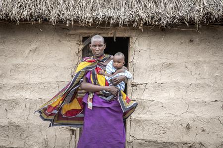 Same, Tansania, 4. Juni 2019: Stolze Massai-Frau mit ihrem Baby, die aus ihrem Haus tritt Editorial