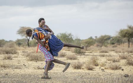 Arusha, Tanzania, 7th September 2019: maasai warriors wrestling in a savannah Editorial