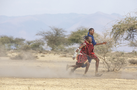 Arusha, Tanzania, 7th September 2019: maasai warriors playing football in savannah