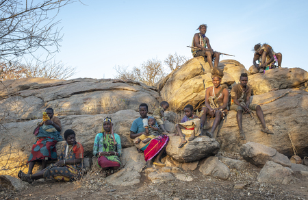 Lake Eyasi, Tanzania, 11th September 2019: Hadzabe men on a rock with his bow and arrows