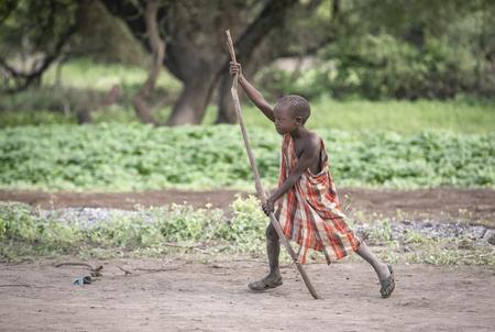 Same, Tanzania, 4th June, 2019:  Maasai kid playing outside his home